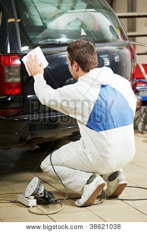 auto mechanic worker preparing car body for polishing at automobile repair and renew service station shop