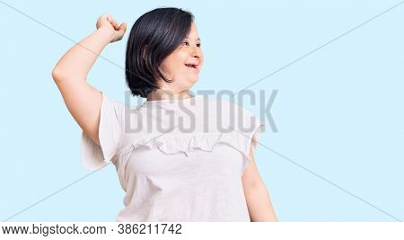 Brunette woman with down syndrome wearing casual white tshirt dancing happy and cheerful, smiling moving casual and confident listening to music