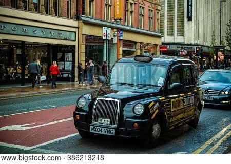MANCHESTER, UK - FEB 24, 2020: Vintage taxi in street with urban architecture in England, United Kingdom
