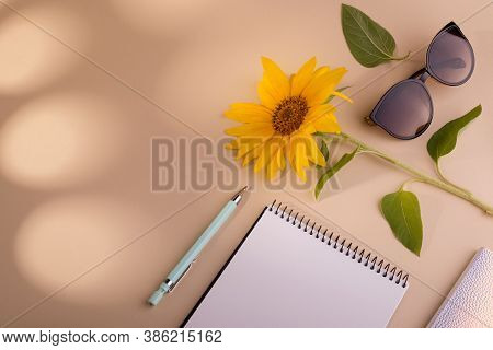 Fashion Flat Lay With Notebook, Sun Glasses, Sunflower, And Pen Against Beige Background. Good For S