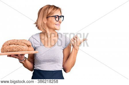 Young blonde woman holding wholemeal bread pointing thumb up to the side smiling happy with open mouth