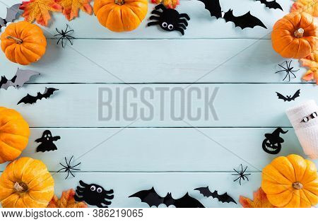 Top View Of Halloween Crafts, Orange Pumpkin, Ghost, Bat And Spider On  Pastel Wooden Background Wit