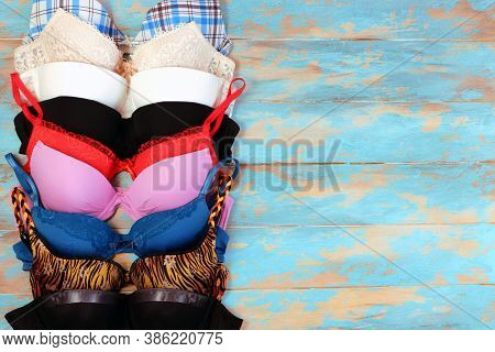 Many Womens Bra On Blue Wooden Background. Underwear Fashion Concept. Basic Lingerie Flatly Top View