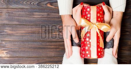 Top View Of Giving And Receiving A Present On Wooden Background. A Man And A Woman Holding Gift In H