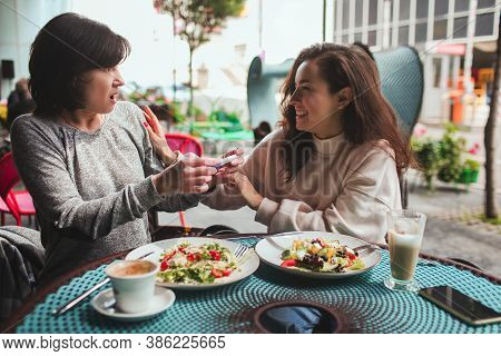 Mature Mother And Her Young Daughter Sit Together In Cafe Or Restaurant. Shocked Mature Woman Hearin