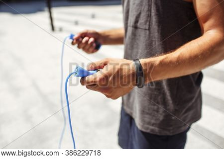 Young Man Exercising Outside. Cut View Of Athletists Hands Holding Blue Jumping Rope And Ready For E