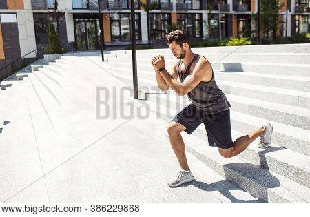 Young Man Exercising Outside. Guy Holding Hands Together And Doing Squat Exercises On One Leg During