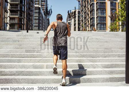 Young Man Exercising Outside. Back View Of Strong Powerful Guy Running Up Steps Outside At Urban Bui