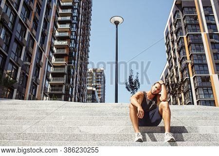 Young Man Exercising Outside. Tired Exhausted Athletist Sitting Alone On Steps Outside Urban View An