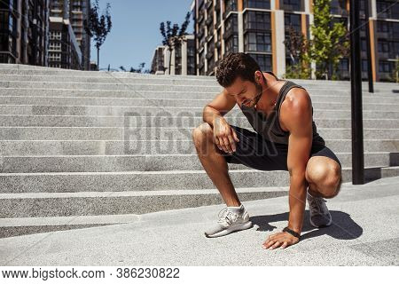 Young Man Exercising Outside. Concentrated Serious Guy Touching Asphalt And Looks Down. Rest After E