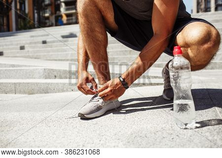 Young Man Exercising Outside. Cut Low View Of Man Tie Laces Of Shoes Or Sneakers. Almost Empty Water
