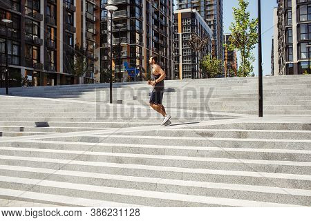 Young Man Exercising Outside. Picture Of Guy Running Or Jogging Alone Outside Near Steps. Urban City