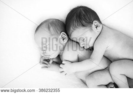 Newborn Twins Sleeping Together In A Hug. Babies Lies Together On Blanket. Sibling Love From Birth -