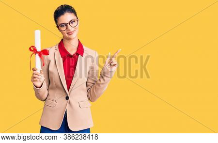 Young beautiful woman wearing glasses holding graduate degree diploma smiling happy pointing with hand and finger to the side
