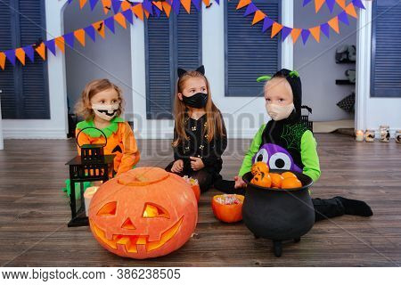 Kids In Carnival Costumes Are Celebrating Halloween, Wearing Face Masks And Playing With Pumpkins An