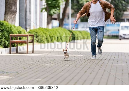 Partial View Of Man With Jack Russell Terrier Dog On Leash Running Along Urban Walkway