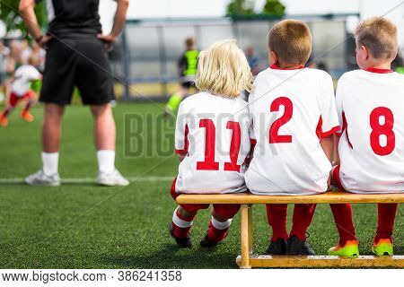 School Kids On Soccer Bench. Group Of School Boys With Coach On A Pitch Sideline On Soccer Football