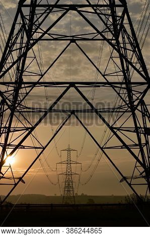 National National Grid Electricity Pylon In Silhouette Framing Distant Pylons Lined Across Agricultu