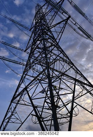 Electricity Pylon Photographed From Below Looking Up At The Steel Lined Structure And Power Lines In