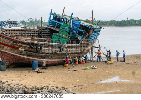 Dar Es Salaam, Tanzania - January 2020: Group Of African Black People Reparing Wooden Fishing Boat O