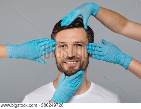 Hands In Protective Medical Gloves Touching Smiling Man Face Over Grey Studio Background. Plastic Su