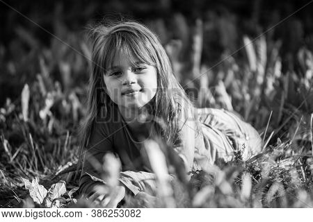 Little girl laying in the grass. Black and white photography.