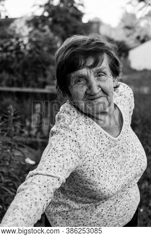 An old woman, selfie outdoors. Black and white photo.