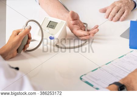 Hand of young female therapeutist pressing pump of tonometer while measuring blood pressure of senior man sitting in front of her