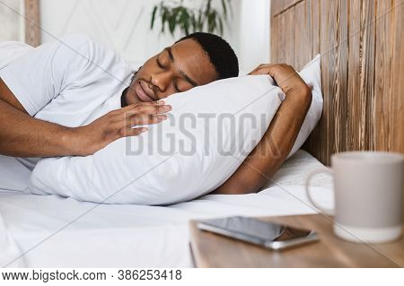 Oversleeping Concept. African American Guy Sleeping Through Alarm Clock In Morning Lying In Bed At H