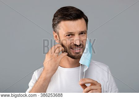 Bearded Man Moved Protective Medical Mask From Face To Scratch Beard, Grey Studio Background, Free S