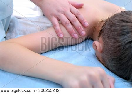 Doctor Massagist Making Therapeutic Massage To Teen Boy On Shoulder In Clinic, Closeup View. Child B