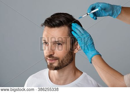 Mesotherapy For Hair. Attractive Man Receiving Injections In His Head, Grey Studio Background. Man H