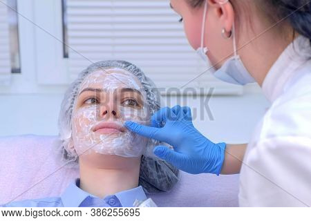 Cosmetologist Is Applying Cream With Anesthesia On Patients Face Skin Before Biorevitalization Proce