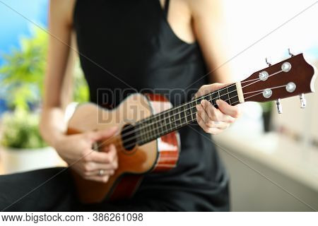 Close-up Of Person Playing Melody On Ukulele. Female Elegant Hand Pressing On String. Musical Talent