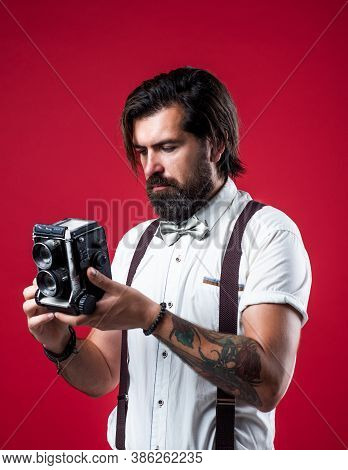 Brutal Bearded Man In Suspenders Holding Retro Camera While Standing Against Red Background, Photogr