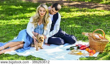 Couple In Love Enjoy Picnic Time. Spring Date. Playful Couple Having Picnic In Park. Couple Cuddling
