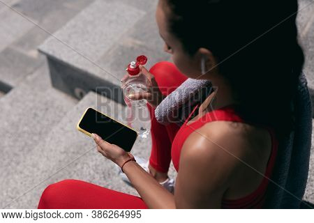 Fit Young Woman With Dark Hair In Red Sportswear And White Earphones Holds Smartphone And Water Bott