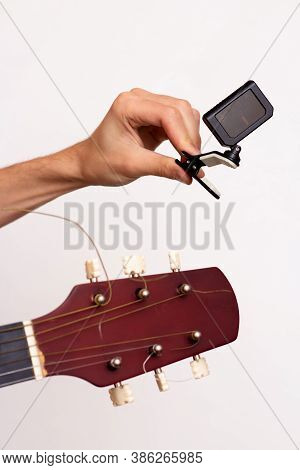 Guitar Tuner. Wooden Guitar On A White Background. Guitar Tuning. The Guy Tunes The Guitar.