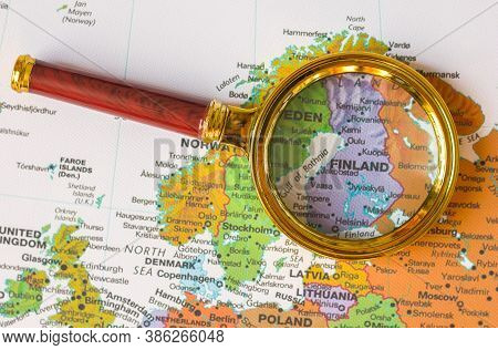 Finland, Helsinki On A Map Of Europe In A Defocused Magnifying Glass, The Theme Of Travel And Trips