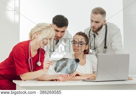 Training With Interns. A Young Blonde Doctor Gives A Lecture To Young Interns In The Office, Discuss
