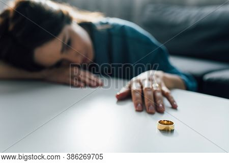 Selective Focus Of Upset Woman Reaching Golden Ring On Coffee Table, Divorce Concept