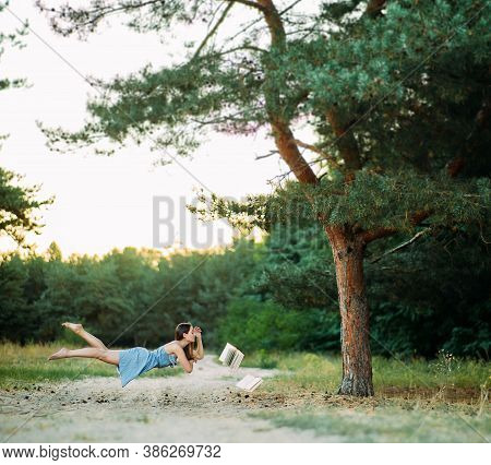 Young Woman Levitates In Forest And Reads Books Flying In The Air Above The Ground.