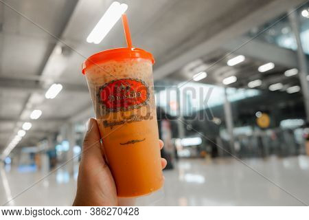 Bangkok, Thailand - September 22, 2020 : Close Up Hand Holding A Glass Of Iced Thai Milk Tea From Th