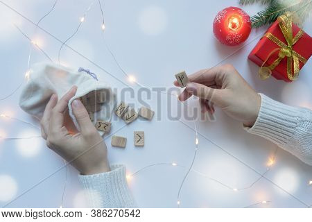 Female Hands In A White Sweater Are Holding Scandinavian Runes. Christmas Divination Concept.