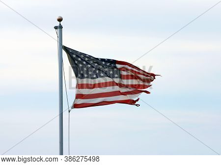 A Tattered And Shredded American Flag Flaps In The Wind On A Flagpole