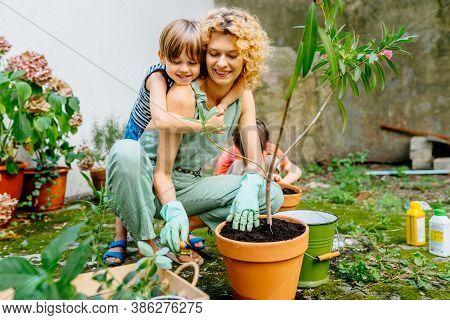 Cute Child Boy Hugging His Mother Gardener At Backyard Garden. Happy Lovely Mom With Children Outdoo