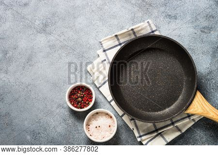 Frying Pan Or Skillet With Stone Nonstick Coating On Light Stone Table. Top View With Copy Space.