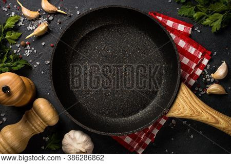 Food Cooking Background With Frying Pan Or Skillet, And Herbs On Black Stone Table. Top View With Co