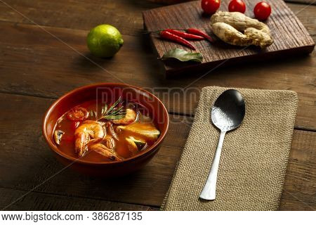 Tom Yam Soup With Shrimp And Lime In A Brown Dish On A Wooden Table Next To A Spoon On A Napkin And