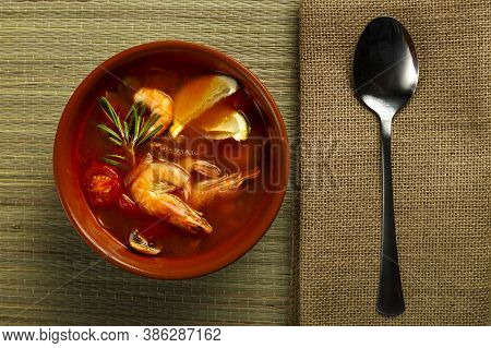 Tom Yam Soup With Shrimp And Lime In A Brown Plate On A Wooden Table Next To A Spoon On A Napkin.